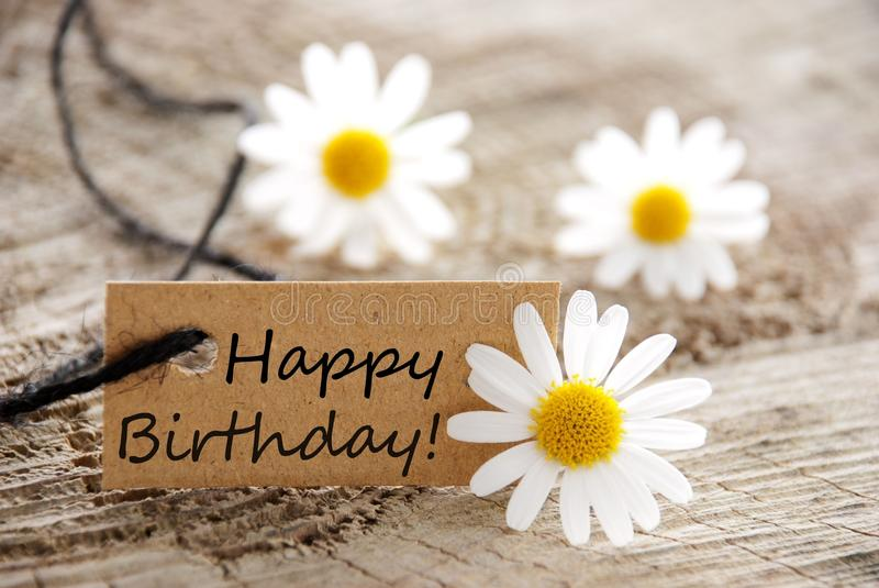 Happy birthday. A natural looking banner with happy birthday and white blossoms as background