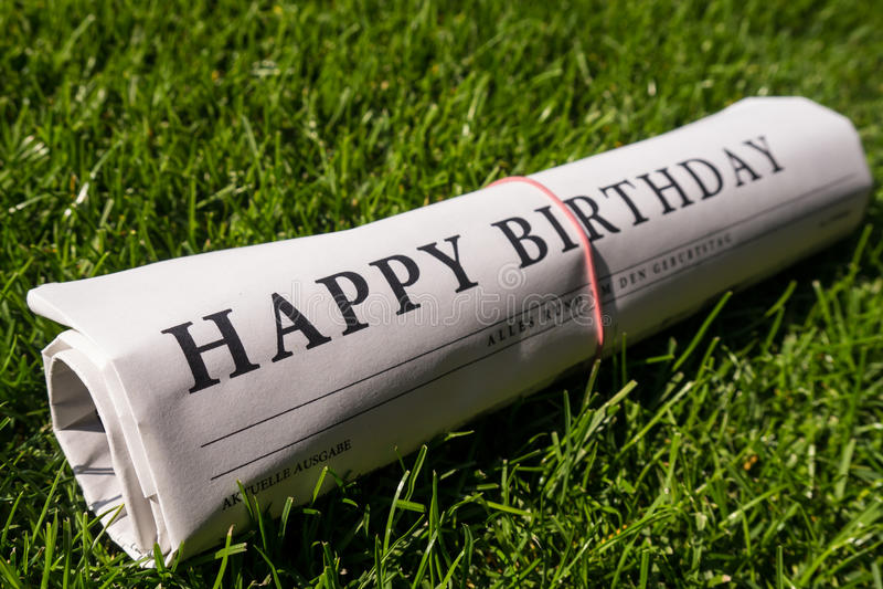 Happy birthday newspaper. On meadow stock image