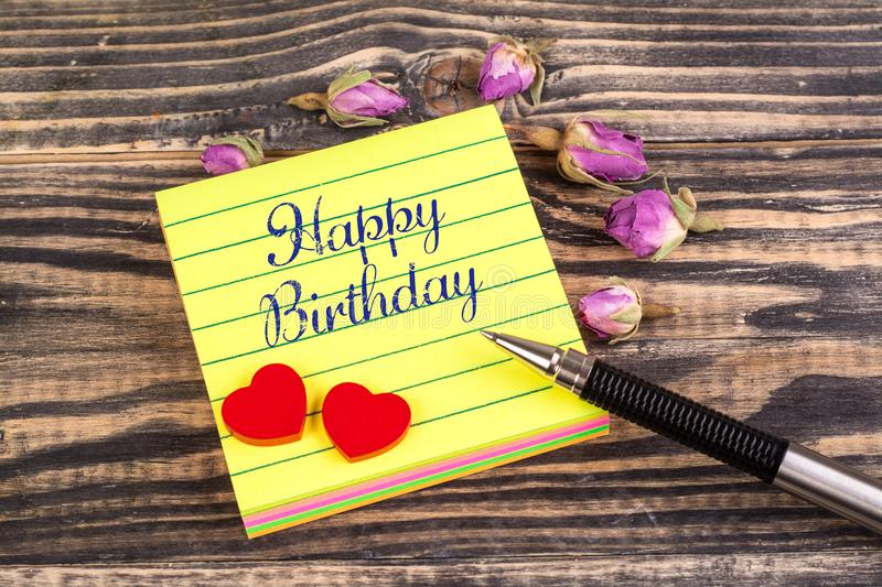 Happy birthday note. Happy birthday in sticky note with tow heart and dried rose buds on wood royalty free stock photo