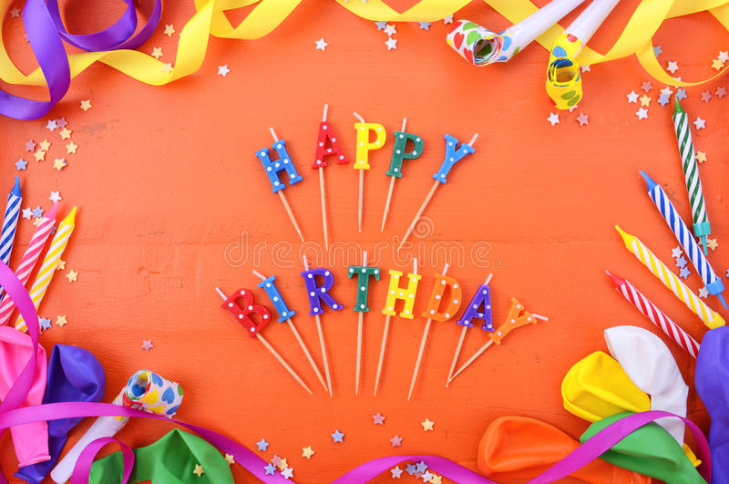 Happy Birthday Party Decorations Background. Happy Birthday background with decorated borders with party decorations on a bright orange wood table with happy royalty free stock photo