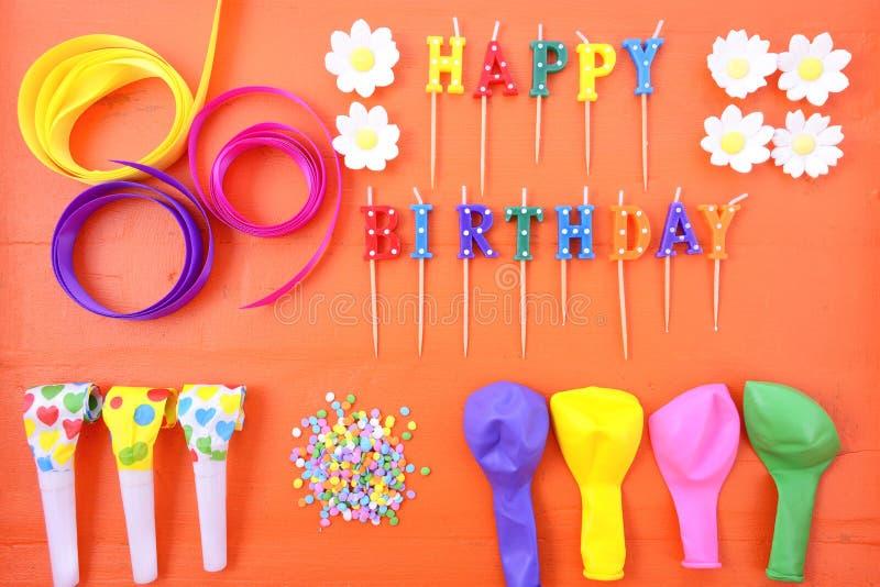 Happy Birthday Party Decorations Background. Happy Birthday flat lay with party decorations on a bright orange wood table stock photo