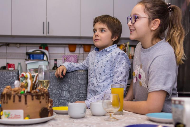 Happy birthday party at home. A brother and sister looking at the cake and going to blow out the candle on it. 2019.02.09, Maloyaros;avets, Russia. Happy royalty free stock image