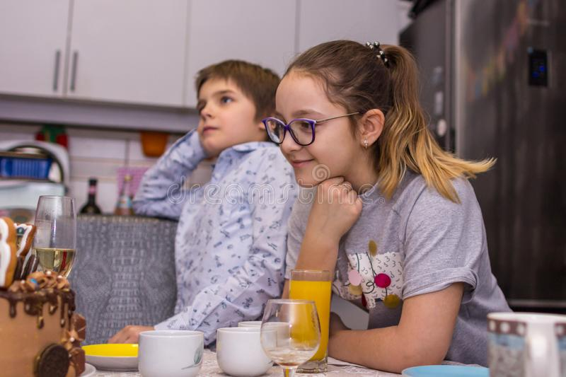 Happy birthday party at home. A brother and sister looking at the cake and going to blow out the candle on it. 2019.02.09, Maloyaros;avets, Russia. Happy stock image
