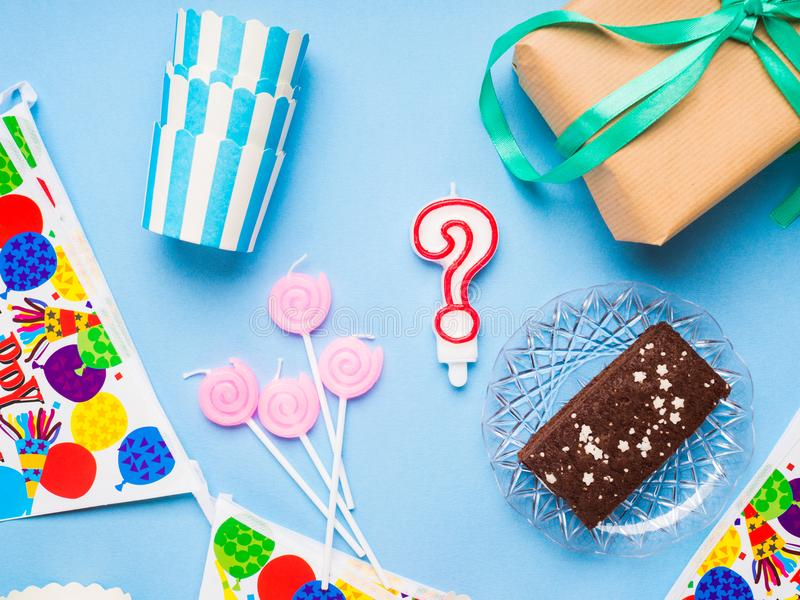 Happy Birthday party items flat lay. Gift box, decoration banner, paper glasses, chocolate cake. Question mark candle royalty free stock photos