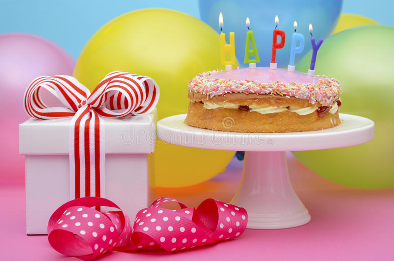 Happy Birthday Party Table. Bright colorful party table with balloons and gifts with bright color ribbons and bows, and Happy Birthday cake on cake stand royalty free stock images