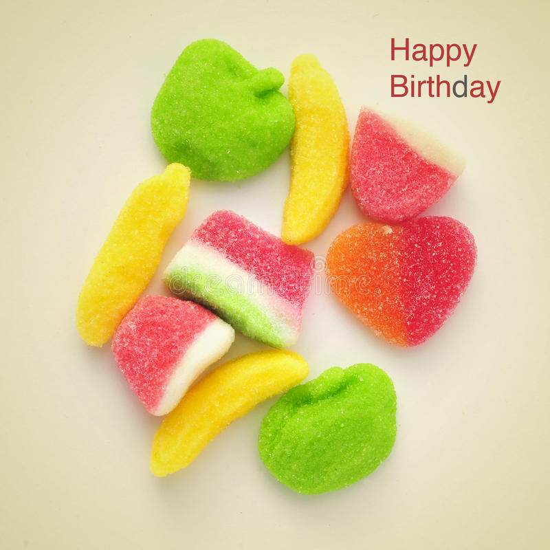 Happy birthday. Picture of some different gummy candies and the sentence happy birthday on a beige background, with a retro effect royalty free stock images
