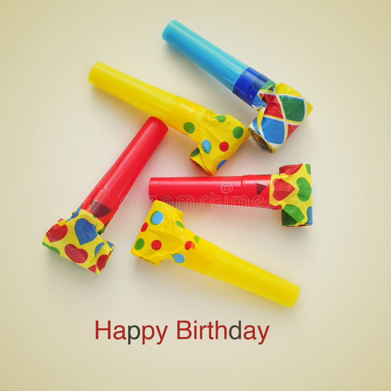 Happy birthday. Picture of some party horns of different colors and the sentence happy birthday on a beige background, with a retro effect royalty free stock images