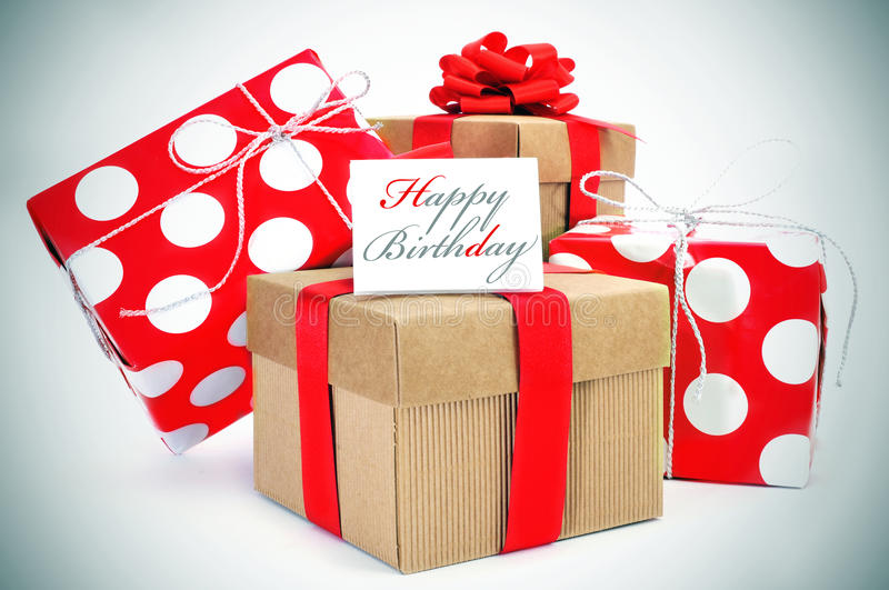 Happy birthday. A pile of gifts and the sentence happy birthday written in a cardboard stock photography