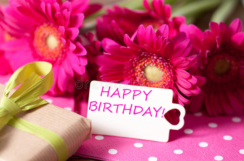 Happy birthday. Pink flowers and card with lettering happy birthday stock photo