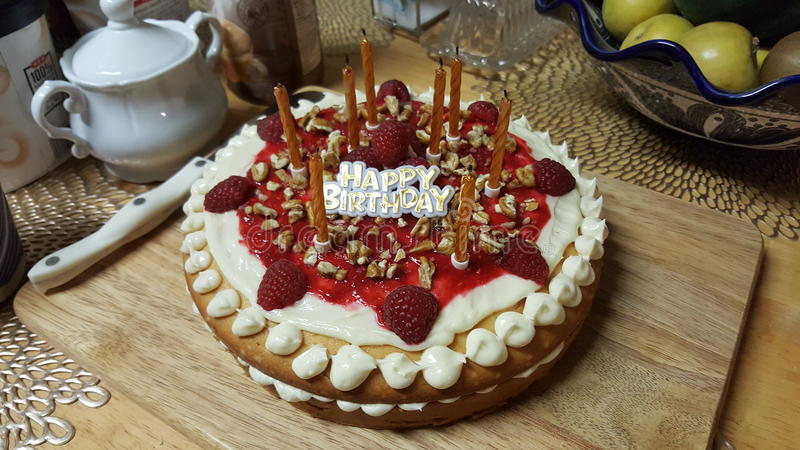Happy Birthday - Raspberry Cake. Homemade white cake with cream cheese frosting, raspberry jam & halves, with pecan bits sprinkled on top stock image