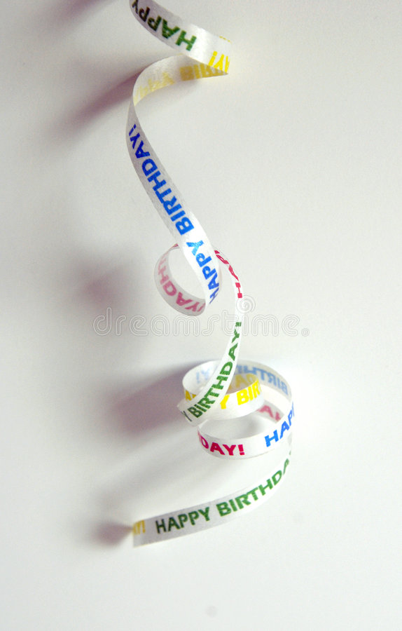 Happy birthday ribbon. A curly piece of white ribbon with colored happy birthday text on it on a white background stock photos