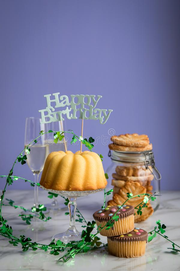Happy birthday ring cake, cookies, biscuits, muffins and champagne  with clover decoration on marble table and lilac background royalty free stock photos