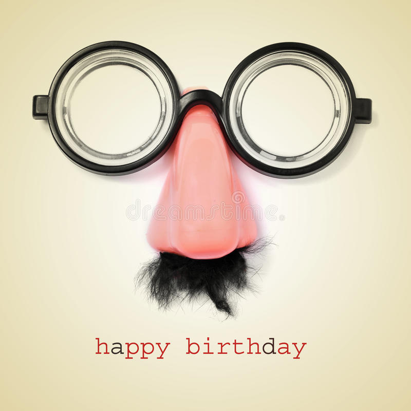 Happy birthday. Sentence happy birthday and fake eyeglasses, nose and mustache on a beige background, with a retro effect stock image