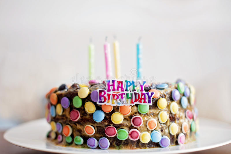 Happy Birthday sign and candles on child candy cake. Happy Birthday sign and candles on child chocolate candy cake stock image