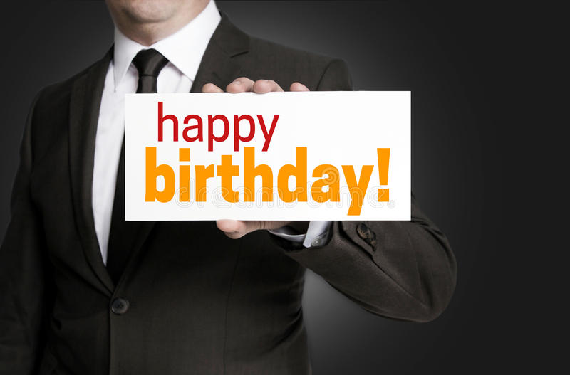 Happy birthday sign is held by businessman stock photo