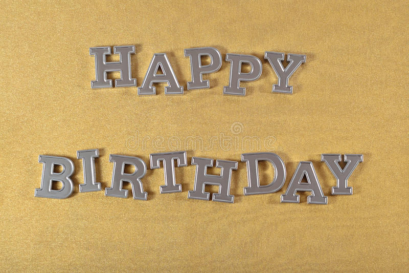 Happy birthday silver text. On a golden background stock photos