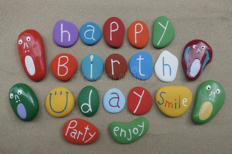 Happy Birthday with a smile and multicolored stones over beach sand. Multicolored stones design for a creative happy birthday message over beach sand royalty free stock photo