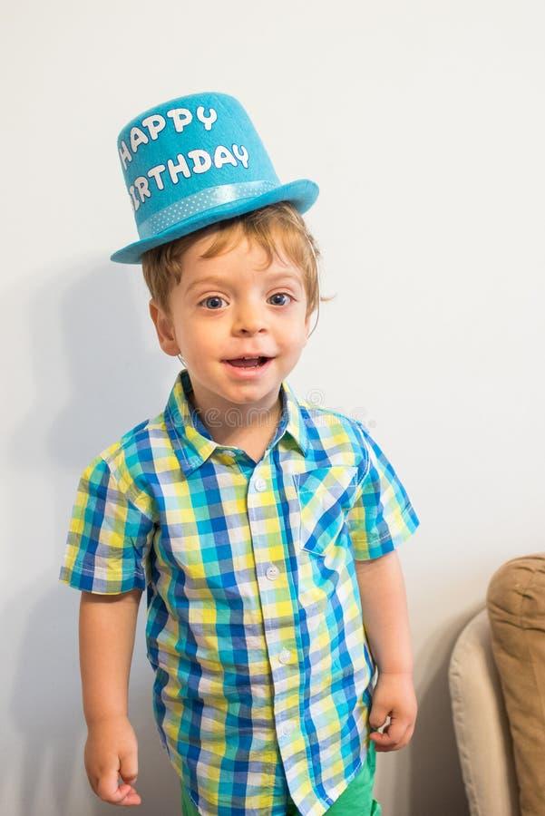 Happy birthday. Smiling  boy. Child portrait. Blond hair and blue eyes child portrait. Wearing a happy birthday hat stock photo