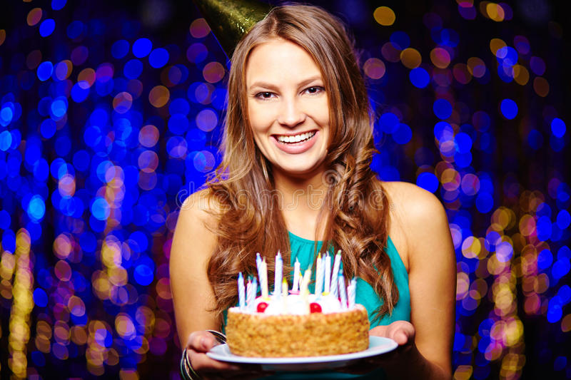 Happy birthday. Smiling girl with birthday cake looking at camera on sparkling background royalty free stock photos