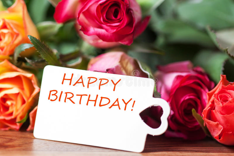 Happy birthday. Some roses and card with lettering happy birthday royalty free stock photos