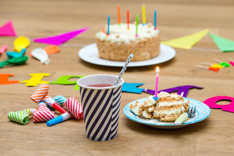 Happy birthday still life with cake and drinks for a chldren's p. Happy birthday party still life with various garlands and objects, including a plate with cake royalty free stock images