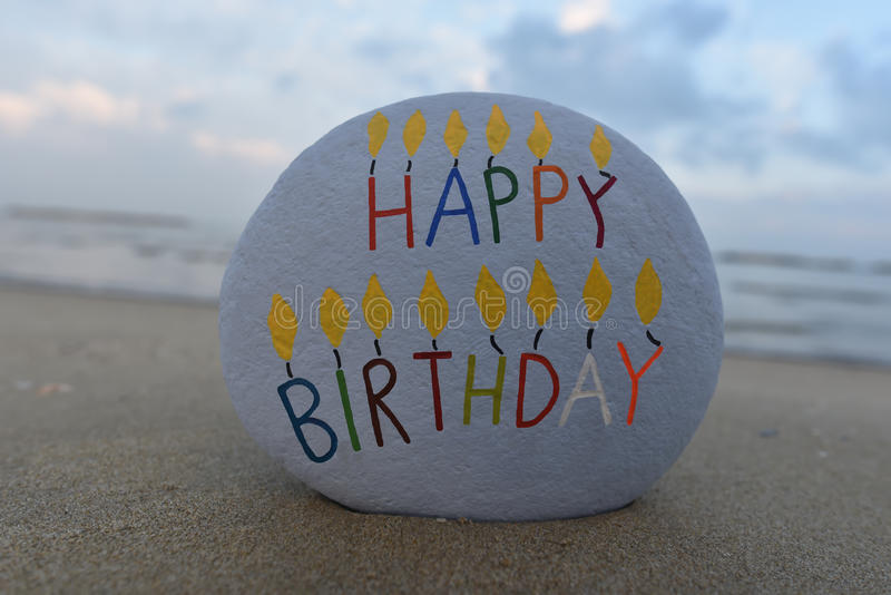 Happy Birthday Stone. A painted stone with the message 'happy birthday' on a beach stock image