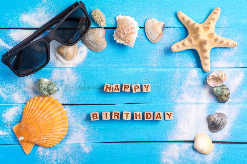 Happy birthday with summer settings concept. Happy birthday On Beach Accessories With Few Marine Items On Blue Wooden Plank , Summer concept stock photo