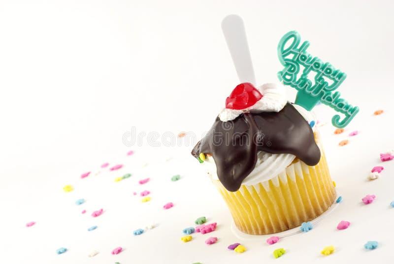 Happy Birthday Sundae Cupcake. With chocolate fudge, whipped cream and cherry, plastic spoon and Happy Birthday decoration copy space stock photo