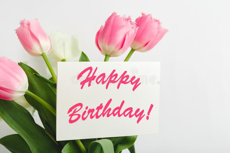 Happy Birthday text on gift card in flower bouquet. Beautiful bouquet of fresh flowers tulips with greeting card Happy Birthday on. White background stock photos