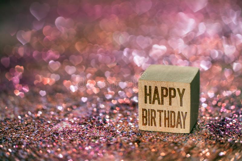Happy birthday text with heart bokeh light. Happy birthday text written on wooden cube on color glitter with beautiful real heart shape bokeh light stock photo