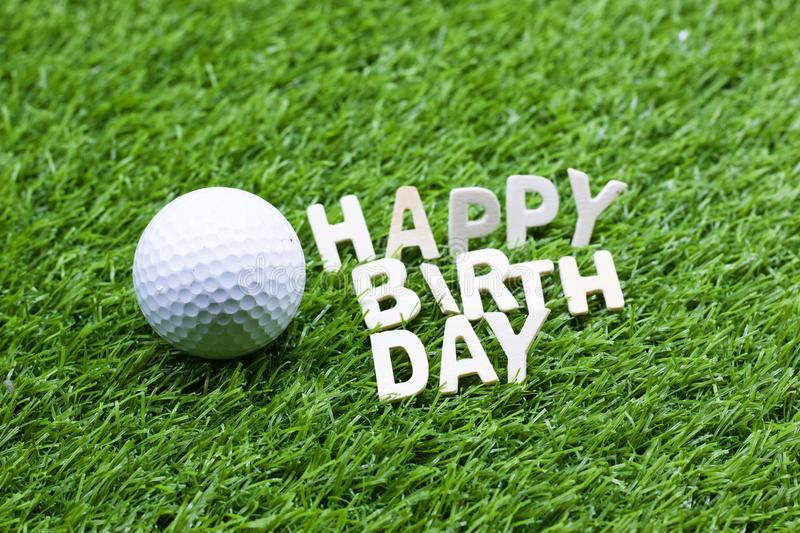 Happy birthday to golfer. With golf ball and letters are on green grass stock image
