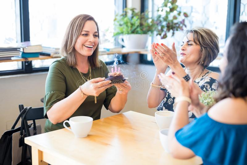 Happy birthday to you. Cute young women celebrating her birthday with friends at coffee shop, she has blown off the candles on cupcake and friends singing stock image