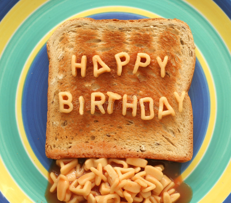 Happy birthday toast. Happy birthday written with alphabetti spaghetti pasta shapes on toast royalty free stock image
