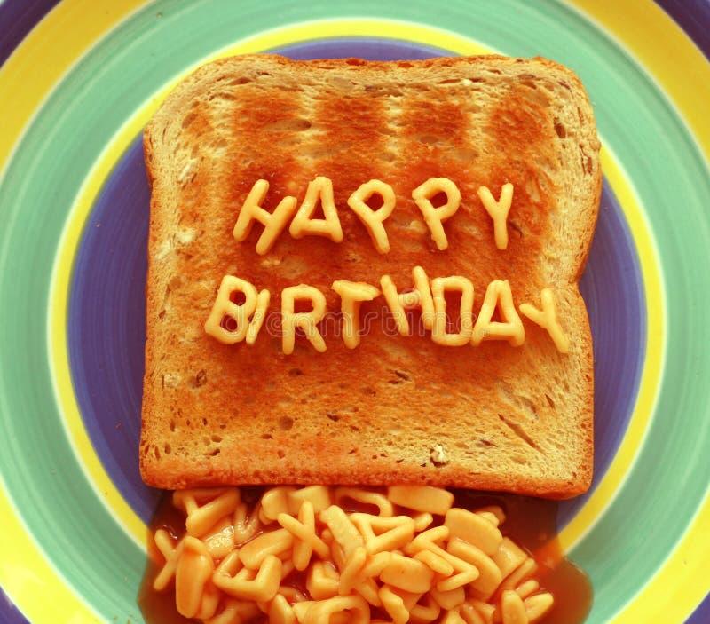 Happy birthday toast. Happy birthday written with alphabetti spaghetti pasta shapes on toast stock photo