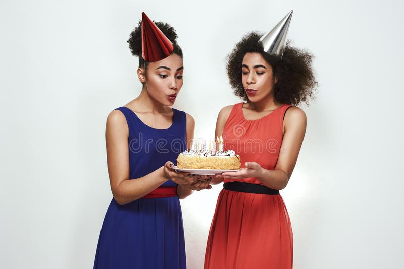 Happy birthday! Two attractive and young afro american women in party hats and evening dresses are blowing out the royalty free stock images