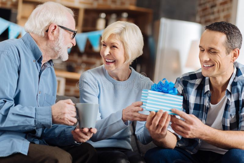 Cheerful man giving present to his elderly mother. Happy birthday. Upbeat young men sitting on the sofa next to his elderly parents and giving a birthday present stock image