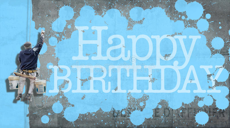 Happy Birthday wall blue. Painter hanging from harness painting a wall with the word Happy Birthday in blue royalty free stock photo