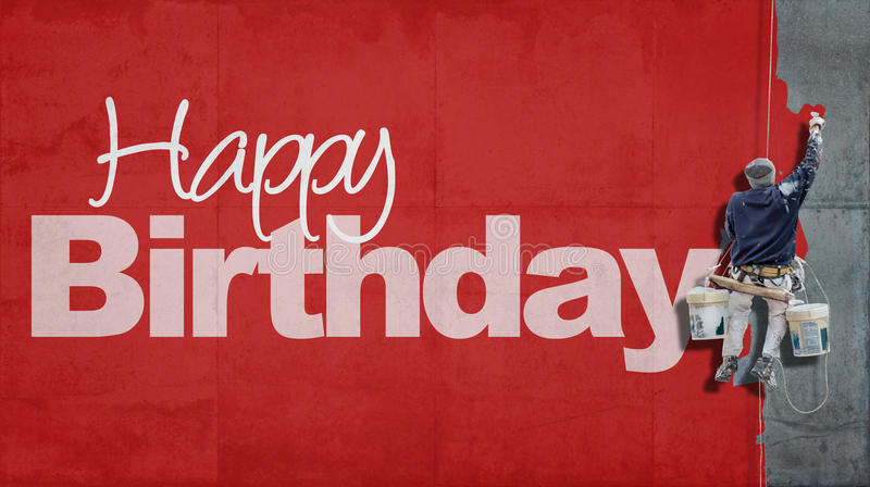 Happy Birthday wall red. Painter hanging from harness painting a wall with the word Happy Birthday in red royalty free stock photo