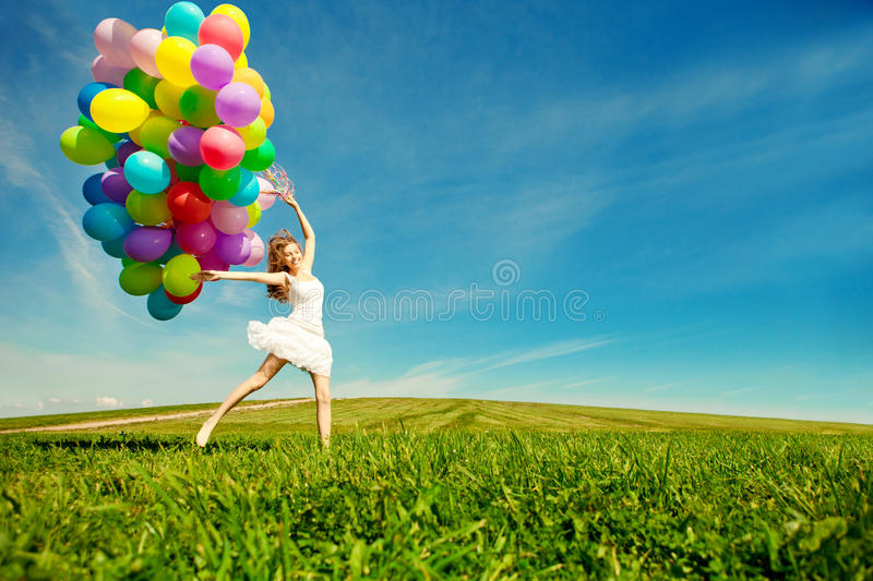 Happy birthday woman against the sky with rainbow-colored air ba. Lloons in hands. sunny and positive energy of nature. Young beautiful girl on the grass in the stock photography
