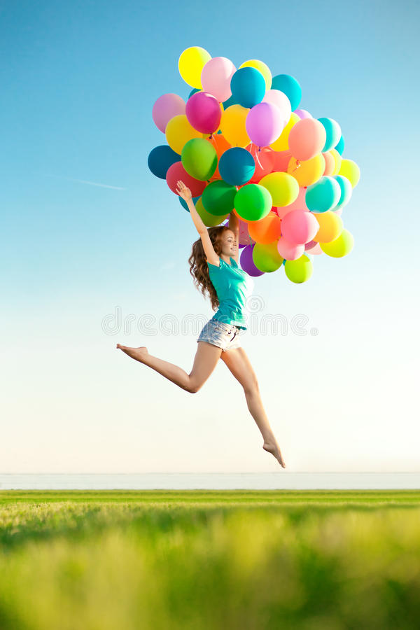 Happy birthday woman against the sky with rainbow-colored air ba. Lloons in hands. sunny and positive energy of nature. Young beautiful girl on the grass in the royalty free stock photos