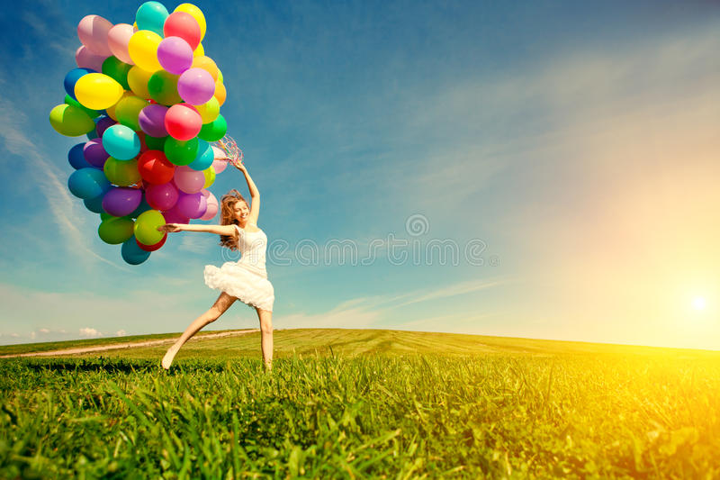 Happy birthday woman against the sky with rainbow-colored air ba. Lloons in hands. sunny and positive energy of nature. Young beautiful girl on the grass in the royalty free stock photography