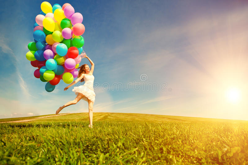 Happy birthday woman against the sky with rainbow-colored air ba. Lloons in hands. sunny and positive energy of nature. Young beautiful girl on the grass in the stock photos