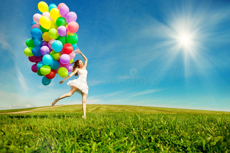 Happy birthday woman against the sky with rainbow-colored air ba. Lloons in hands. sunny and positive energy of nature. Young beautiful girl on the grass in the royalty free stock photo