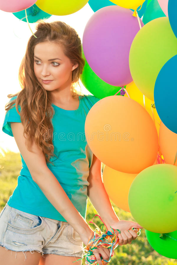 Happy birthday woman against the sky with rainbow-colored air ba. Lloons in her hands. sunny and positive energy of nature. Young beautiful girl on the grass in royalty free stock image