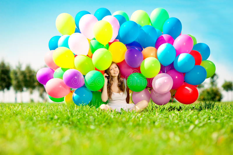 Happy birthday woman against the sky with rainbow-colored air ba. Lloons in her hands. sunny and positive energy of nature. Young beautiful girl on the grass in royalty free stock photo