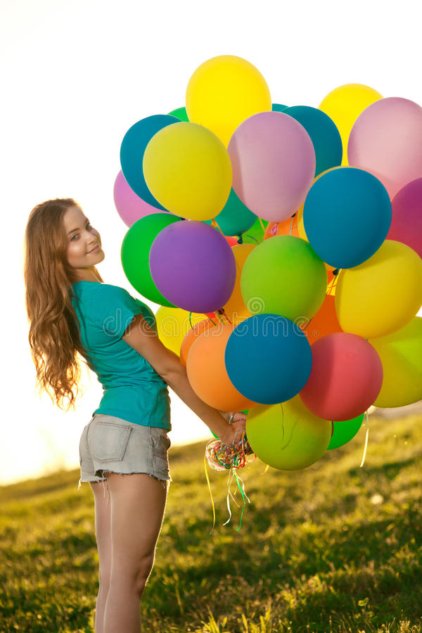 Happy birthday woman against the sky with rainbow-colored air ba. Lloons in her hands. sunny and positive energy of nature. Young beautiful girl on the grass in stock image