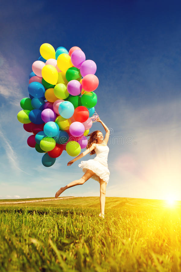 Happy birthday woman against the sky with rainbow-colored air ba. Lloons in her hands. sunny and positive energy of nature. Young beautiful girl on the grass in stock images