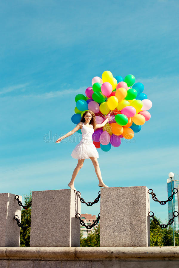 Happy birthday woman against the sky with rainbow-colored air balloons. In her hands. sunny and positive energy of urban street. Young beautiful girl on the royalty free stock photography