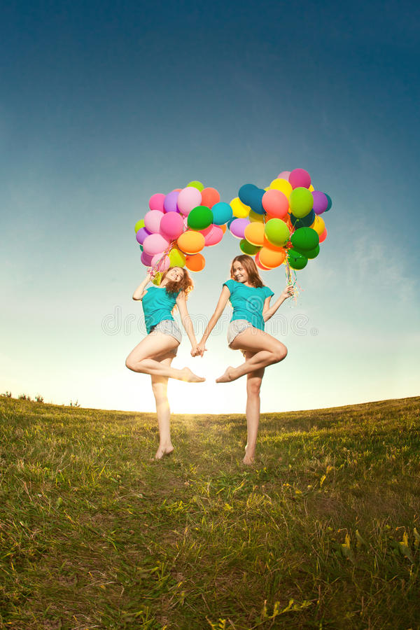 Happy birthday women against the sky with rainbow-colored air ba. Lloons in her hands. sunny and positive energy of nature. Young beautiful girls, twins on the stock images