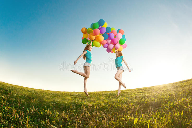 Happy birthday women against the sky with rainbow-colored air ba. Lloons in her hands. sunny and positive energy of nature. Young beautiful girls, twins on the stock photos